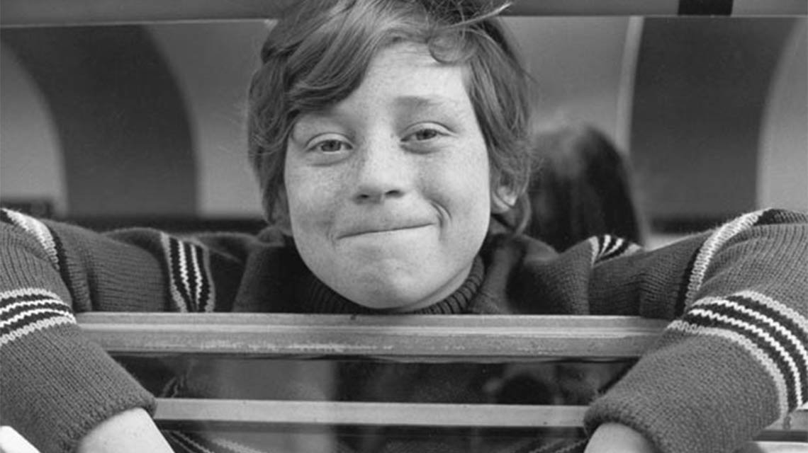Danny Bonaduce looks super cute in black and white picture from his childhood. He is facing directly at the camera with a subtle smile and locked lips. He is leaning on a wooded bar.