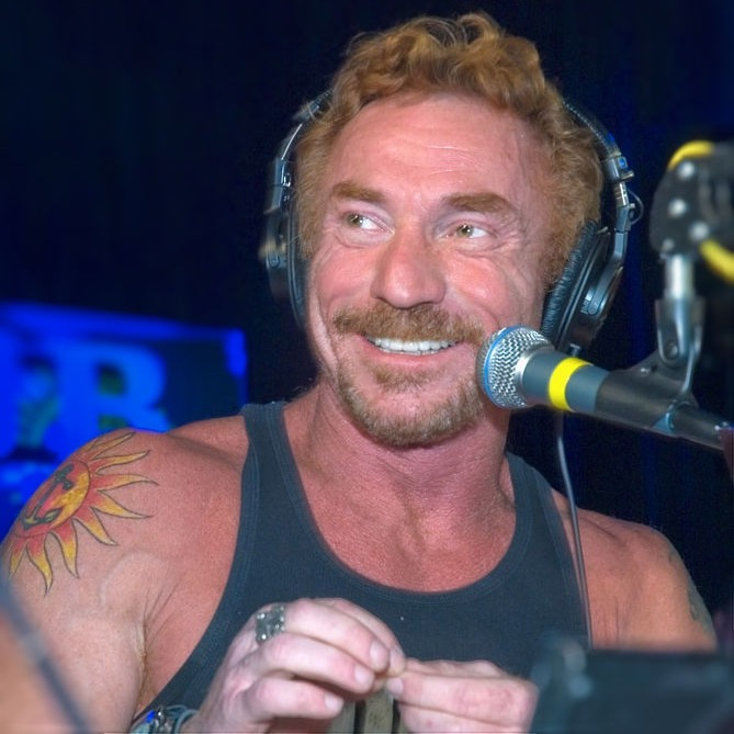 Danny is looking away from the camera and has a bright smile on his face. He has put on a headphone on his head and has a mic in front of him. He is wearing a sleeveless t-shirt which reveals his tattoo located on his right arm.