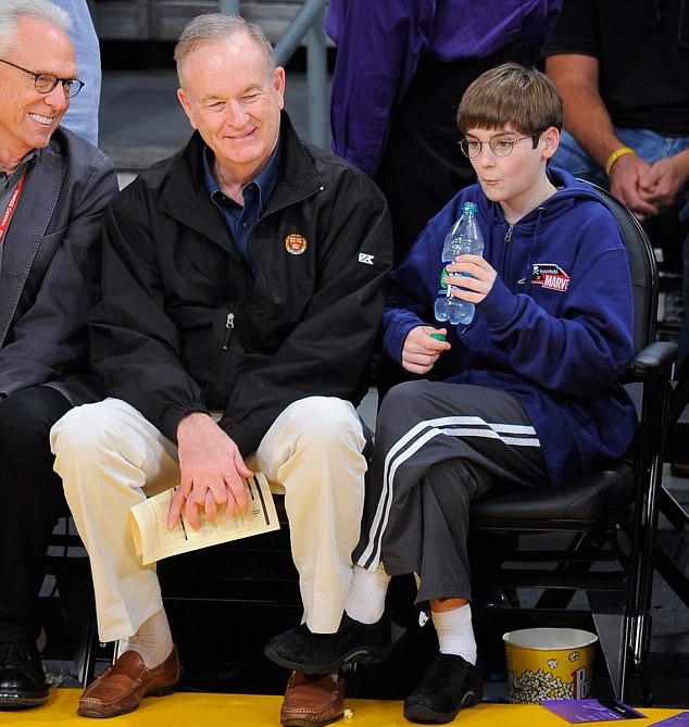 Bill O'Reilly and his son Spencer O'Reilly are sitting next to each other. Bill is holding a paper on his hand while his son is holding a bottle of water.