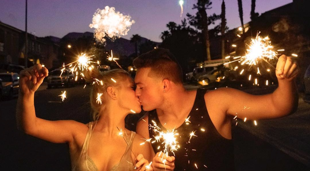 Lance Stewart and his girlfriend Lizzy Wurst are in a lip lock position. They hold lighted firecrackers in their hand as they celebrate the 4th of July.