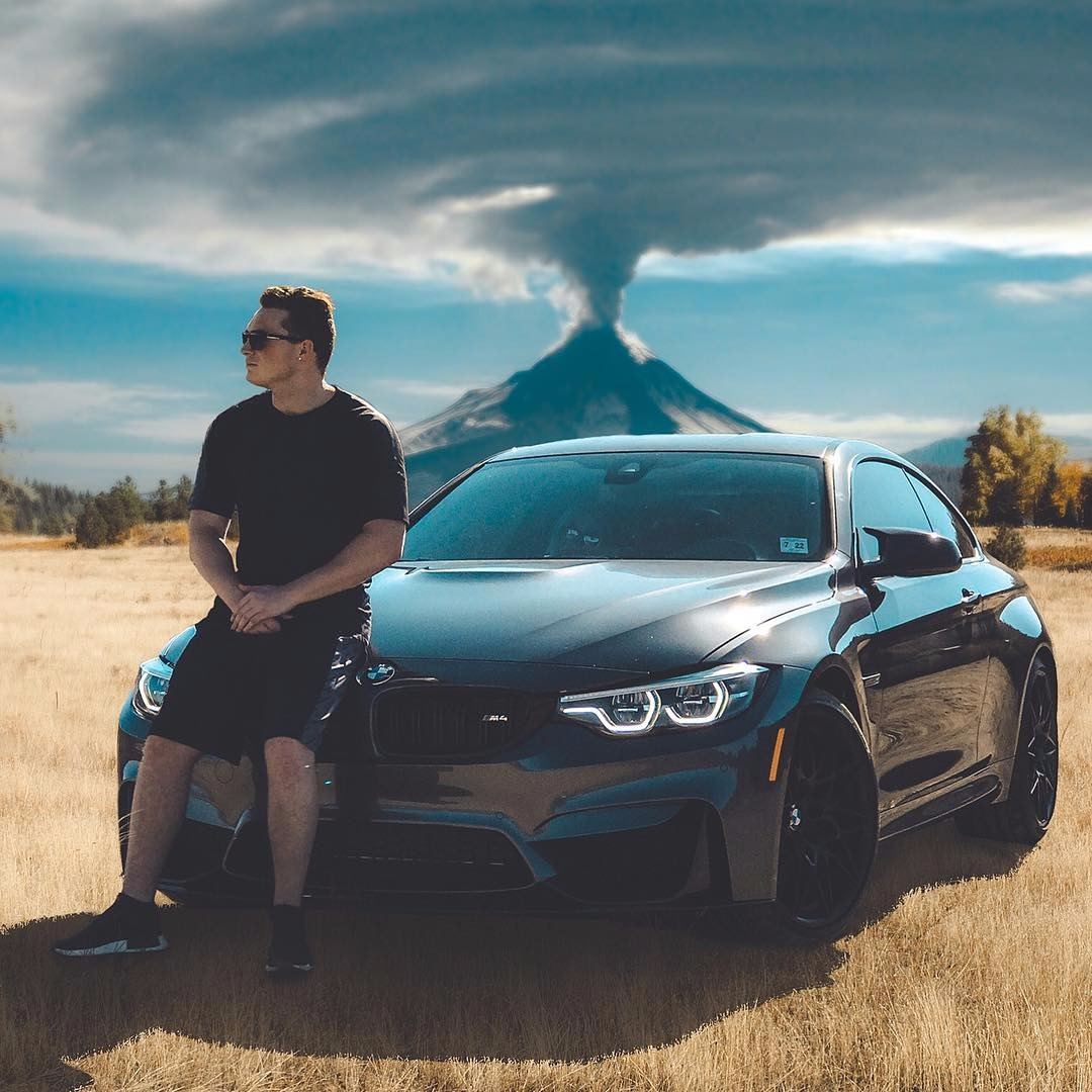 Lance Stewart posing on his new car the 2018 BMW M4. He looks stunning posing with his black beast. He is wearing a plain black tee and shorts with black sports shoes.
