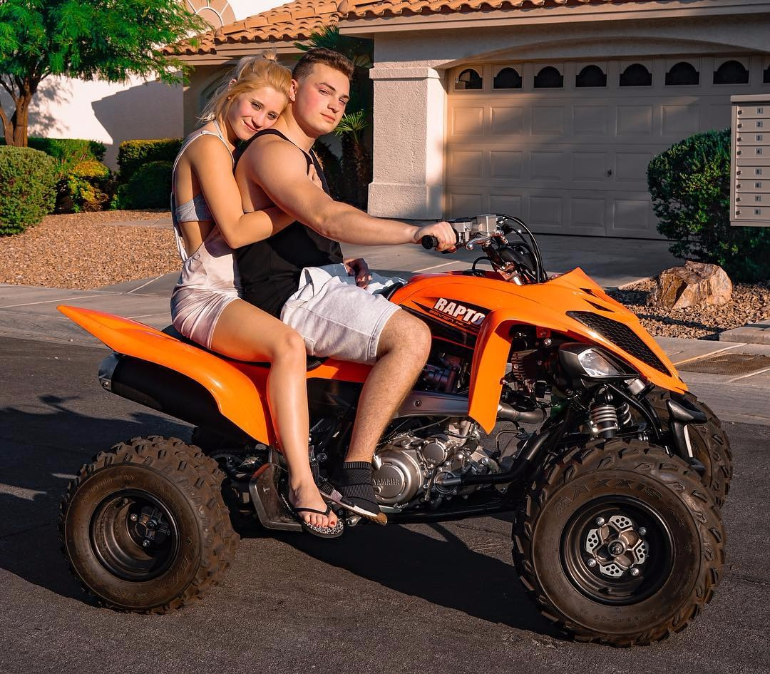 Lance Stewart riding his Raptor Dirt Bike with his girlfriend in the backseat. Lizzy is hugging Lance from the back while he is riding. Lance is wearing casual shorts and a tank top while Lizzy is wearing a short jumpsuit.