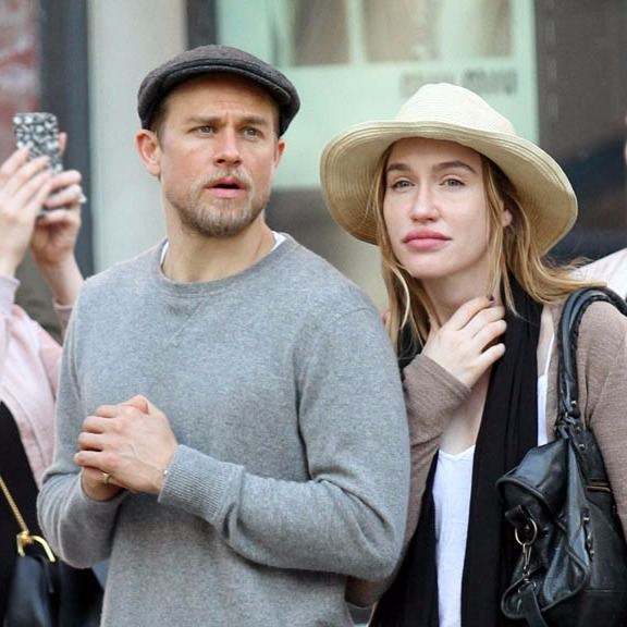 Charlie Hunnam with clasped hands, he's wearing a sweatshirt and a beret, his girlfriend is touching her neck, she's wearing a hat