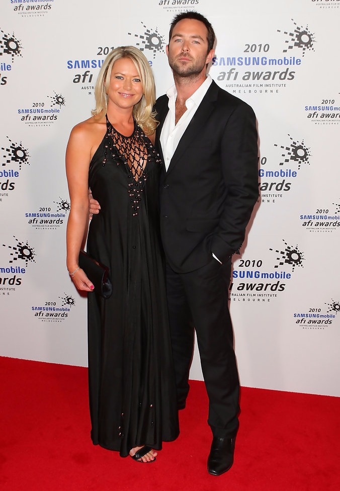 Sullivan Stapleton is holding Jo Beth Taylor by her waist as they stand side by side for a photograph at an award ceremony.