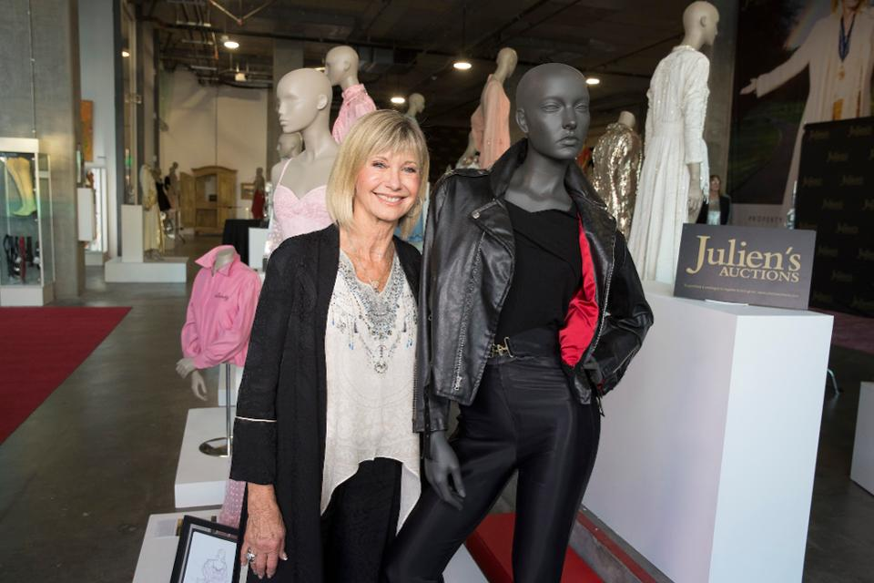 Olivia Newton John alongside the iconic Sandy Olsson outfit from Grease. Olivia Newton John collected $205,700 from selling the outfit which was later given to cancer research facilities in Australia