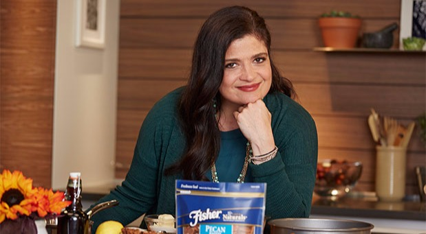 Alex Guarnaschelli posing with a cheerful face on her kitchen