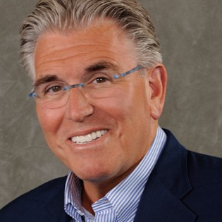 Mike Francesa is smiling at the camera. He is wearing glasses.