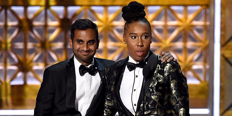 Aziz Ansari is smiling at the audience at Emmy Awards 2017 as he is draping his hand around actress Lena Waithe, with whom he shared the award.