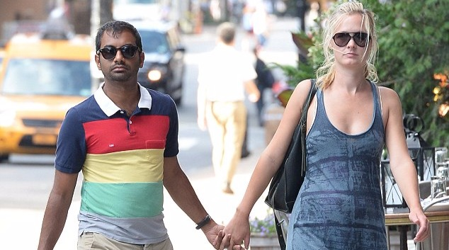 Aziz Ansari and girlfriend Courtney McBroom holding hands, both of them are wearing sunglasses