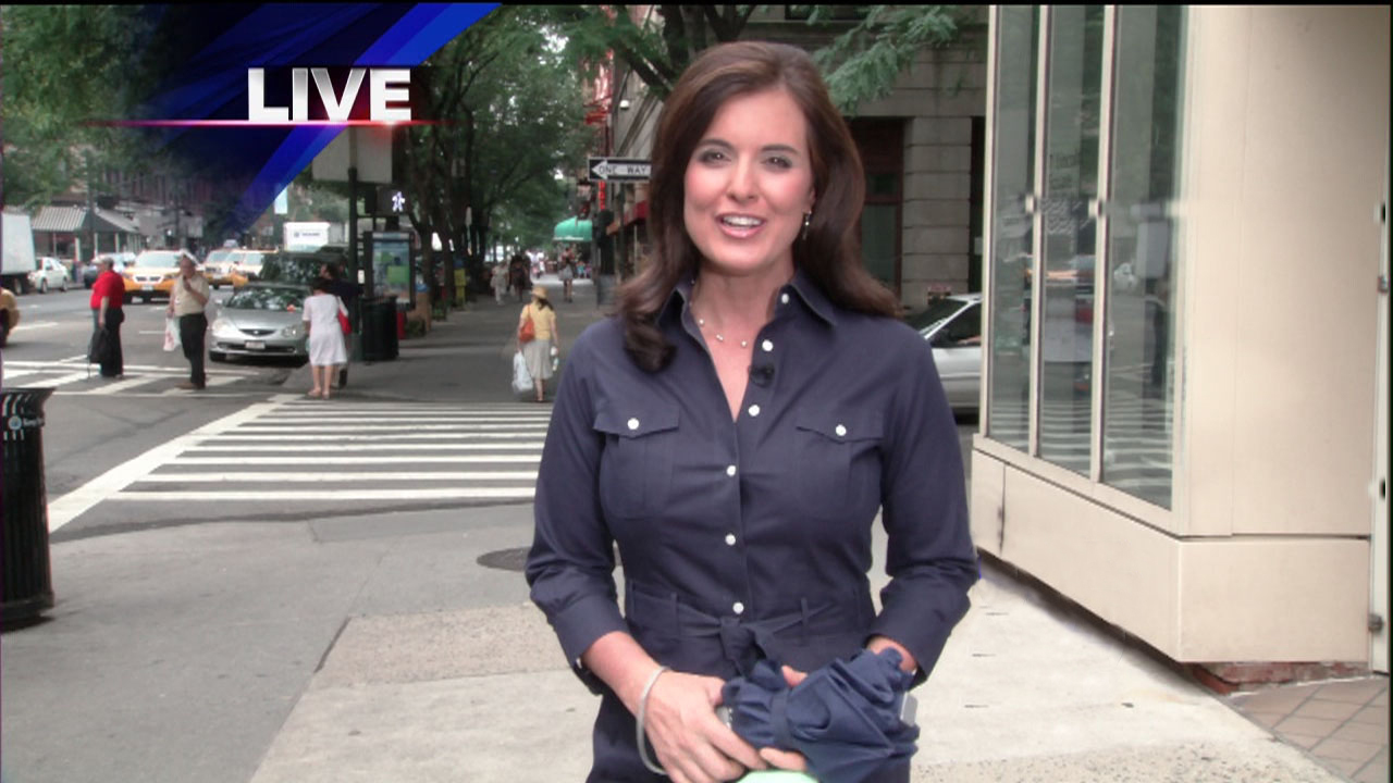 Amy Freeze carrying an umbrella while reporting live from  New York City