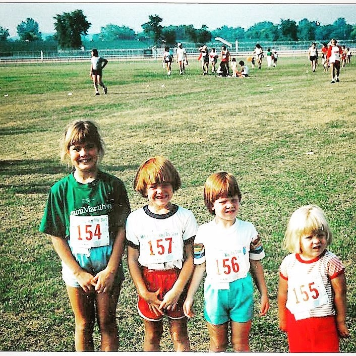 Young Amy Freeze and her three sisters are in a ground with trees in the background. Amy and her sisters are wearing tee-shirt and shorts and have number tagged on their front. Looks like they are getting ready for a marathon.