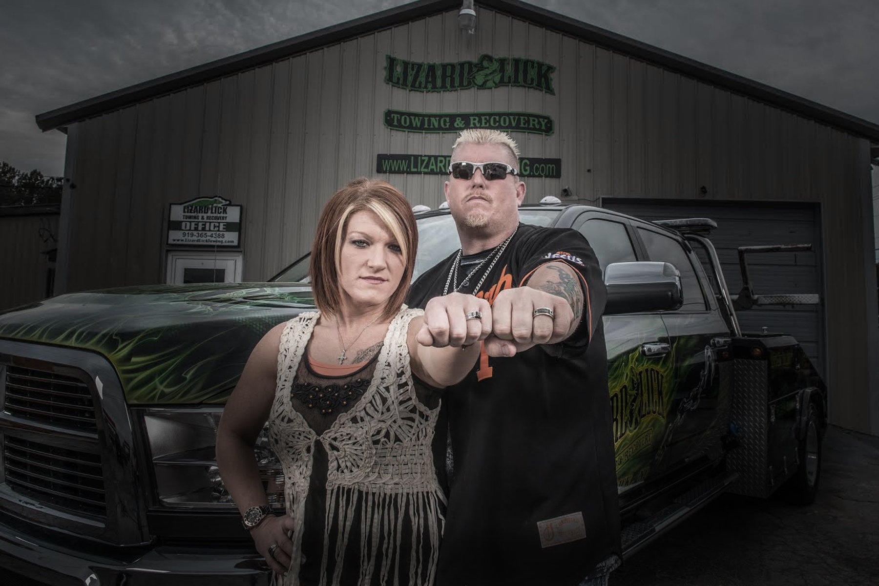 Amy Shirley and her husband, Ron Shirley is standing next to each other. They are putting up their left fist and showing their wedding ring. The pair are standing right in front of the Lizard Lick Towing's building.