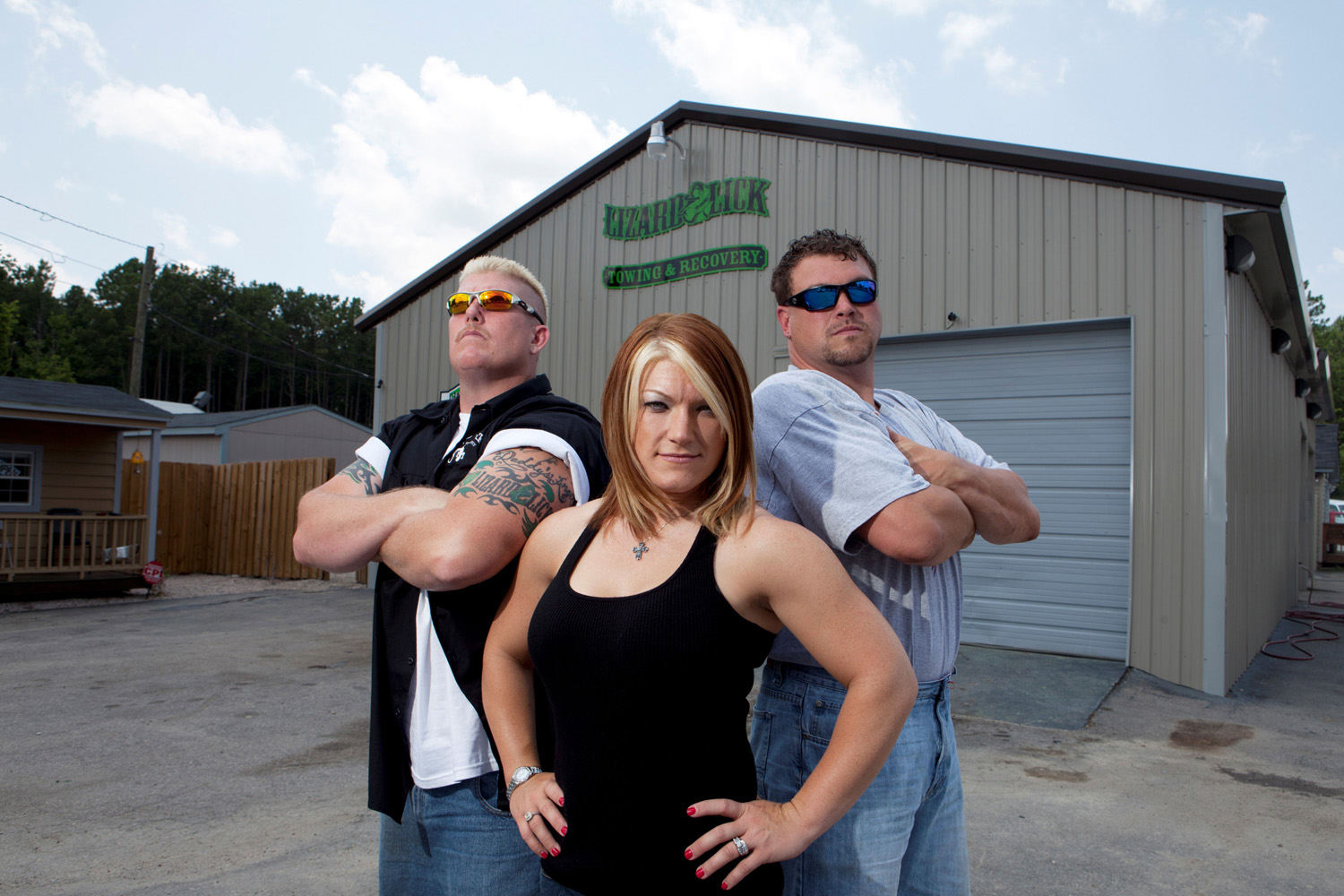 Amy Shirley is standing alongside her husband and a friend. She is wearing a tank top exposing her well toned body. Amy is facing straight at the camera with both her hands rested on her waist. Her husband stands on the left side of Amy with his arms folded and on the side stands a friend.