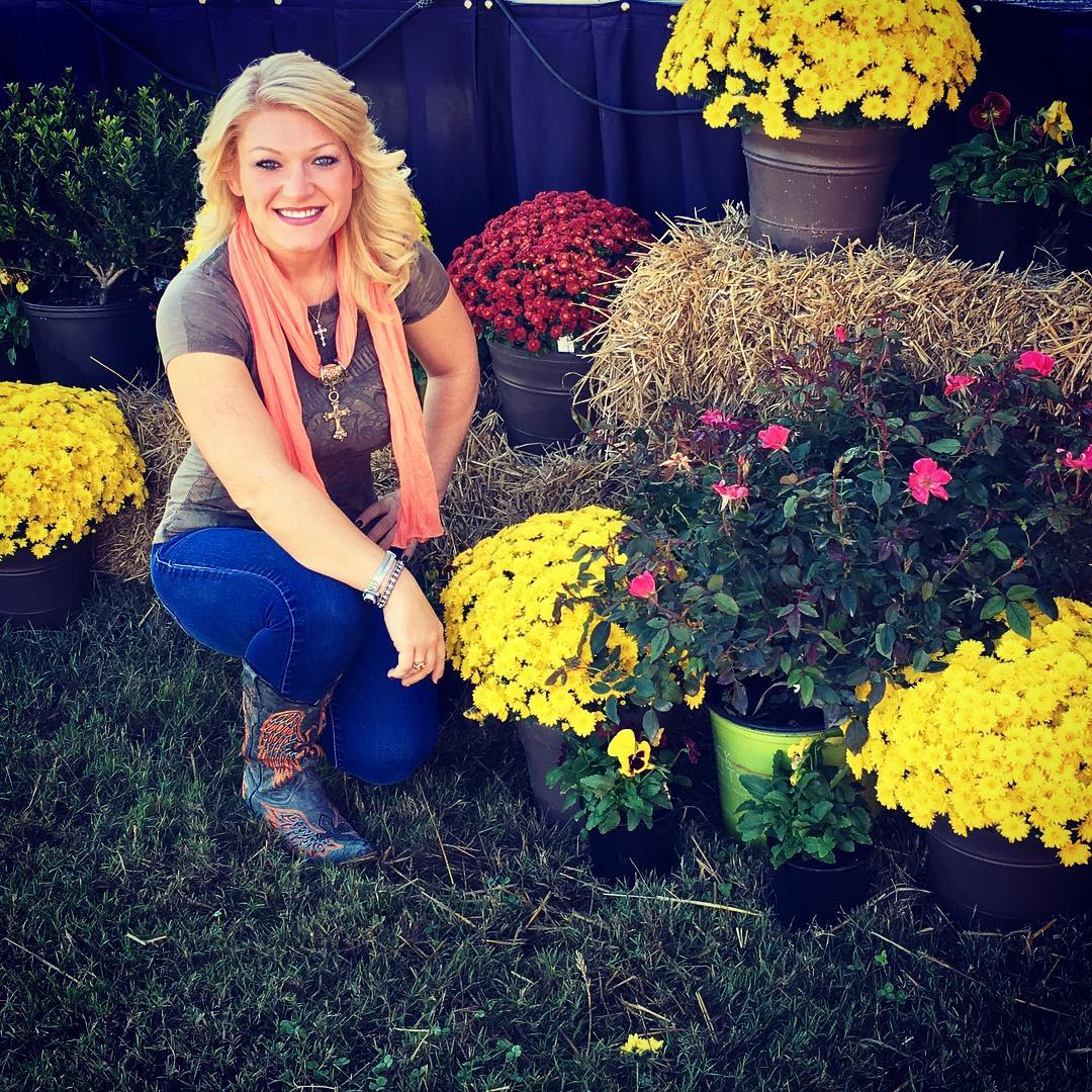 Amy Shirley is sitting in a garden. She is looking straight at the camera with a faint smile on her face. Amy is wearing a brown t-shirt, a blue jeans and a cowboy boot. Her orange shawl is perfectly complimenting with her blonde hair.