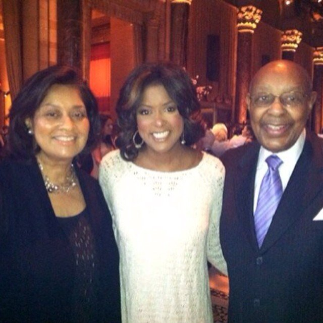Lori Stokes is standing with her mother Jay Stokes to the right and her later father Louis Stokes to the left.
