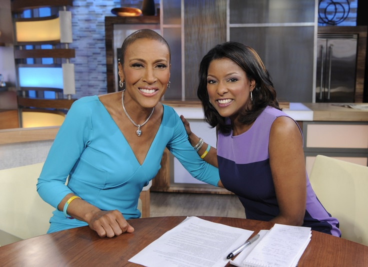Lori Stokes and Robin Roberts are sitting close and embracing each other. There is a pen and papers on the table in front of them.