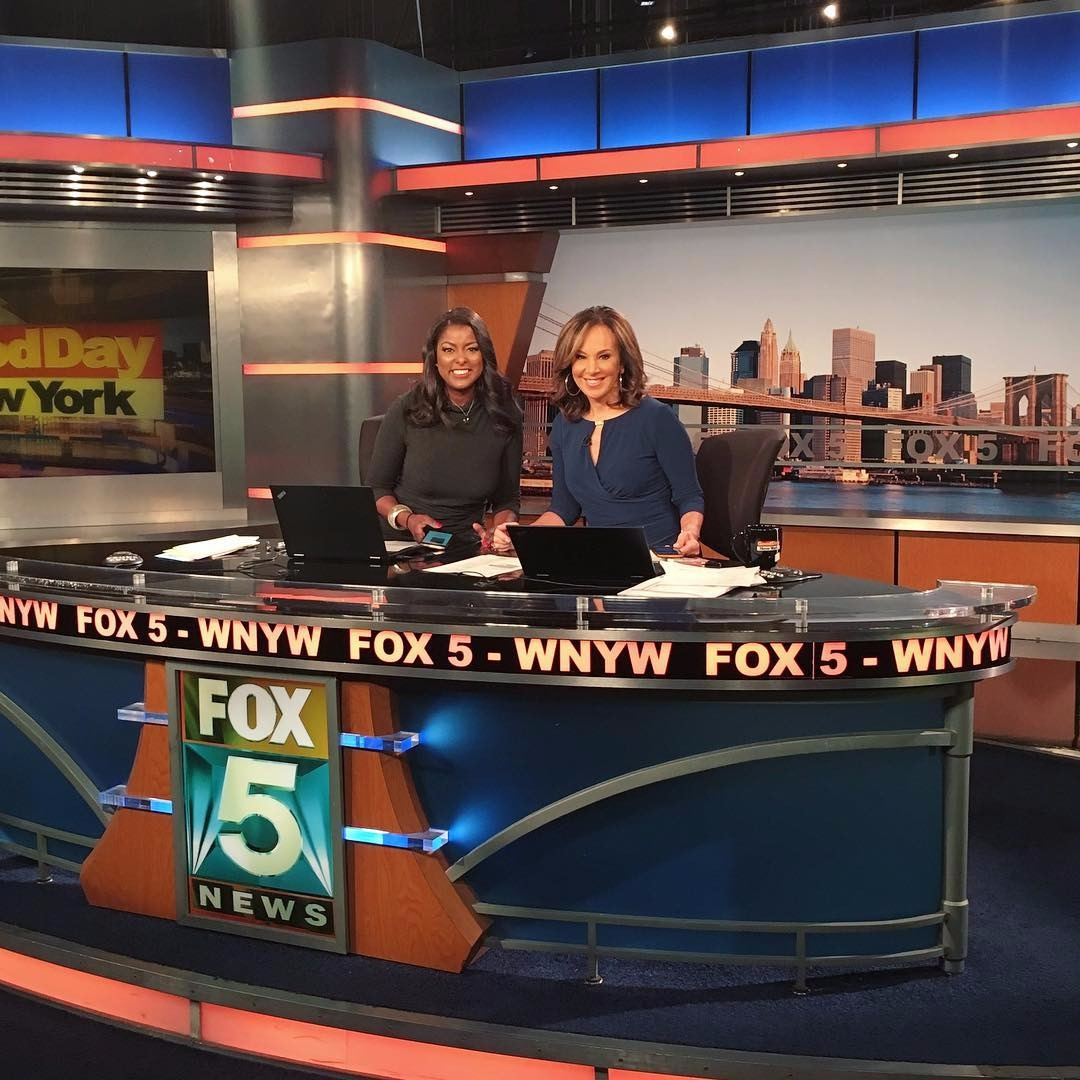 Lori Stokes and Rosanna Scotto behind the table  on the set of Good Day New York.