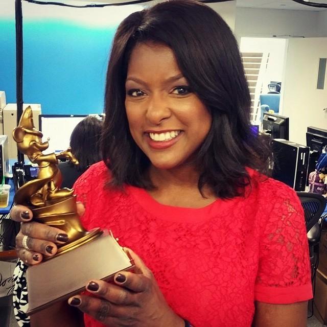 Lori Stokes holding an award