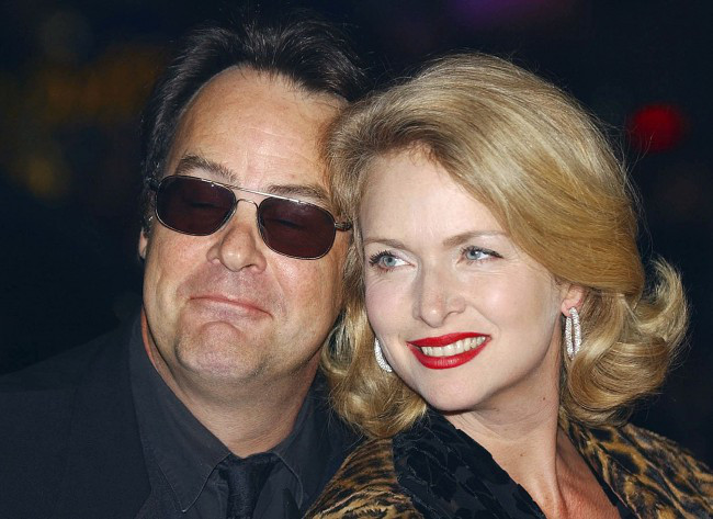 Actor Dan Aykroyd posing with his wife. Here Donna is seen in her blonde hair and Dan is wearing his black shades.