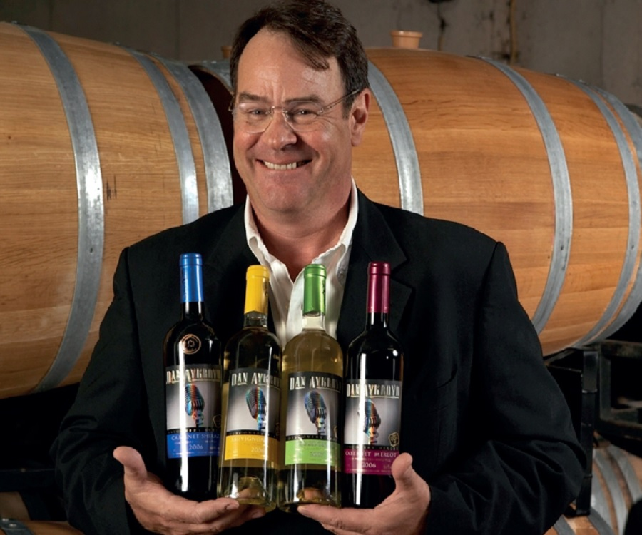 comedian Dan Aykroyd holding 4 bottle of wines and he is smiling at the camera.