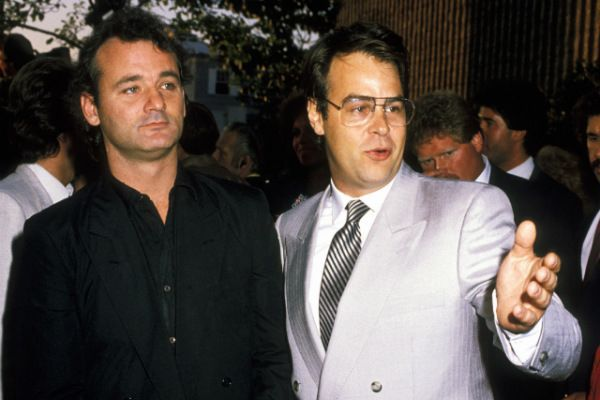 Actor Dan Aykroyd dressed in white coat and Bill Murray in black coat.They are posing for the camera