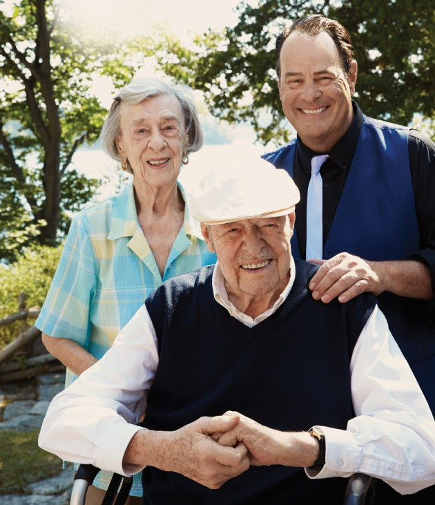 Actor Dan Aykroyd resting his hand on his father shoulder.His father is sitting on chair whereas his mother and he are standing and smiling back.
