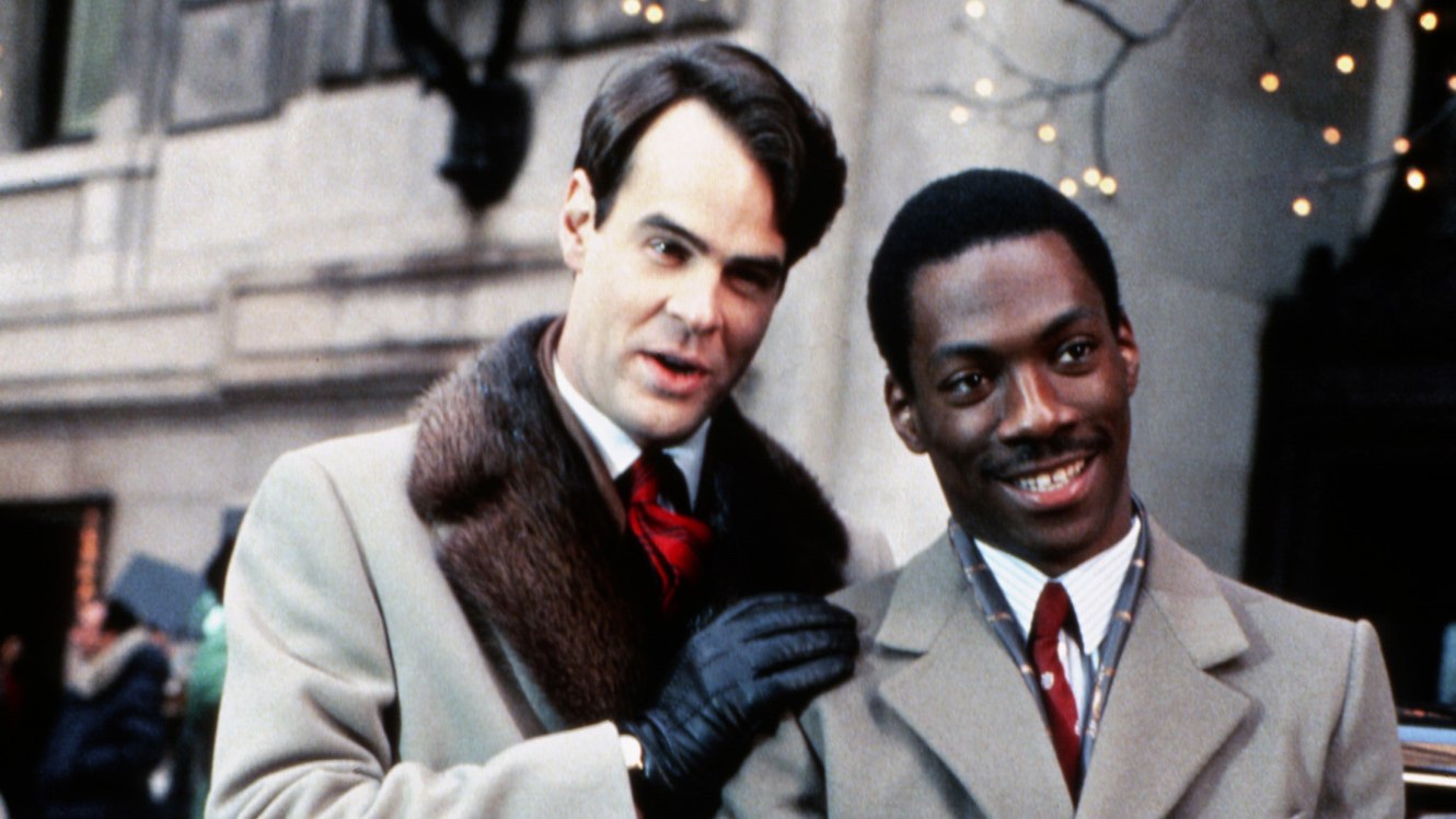 Actor Dan Aykroyd in long furry coat resting his hand on Eddie Murphy. They are smiling at the camera.