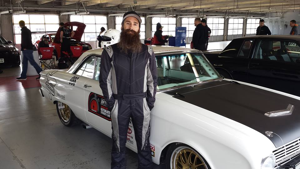 Bearded guy Aaron Kaufman poses in front of a car