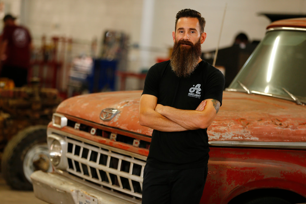 Aaron Kaufman gives intense look and stands taking support of the car