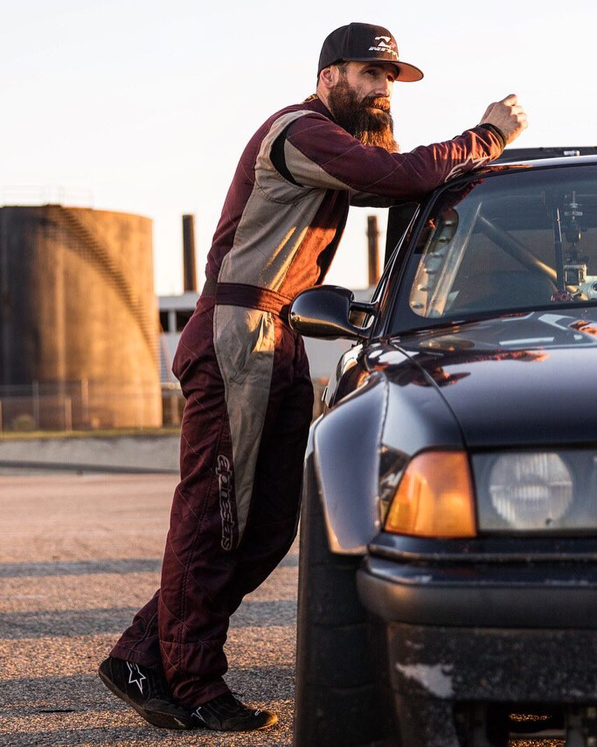 Founder of Arclight, Aaron Kaufman leaning on a BMW, he's wearing a track suit