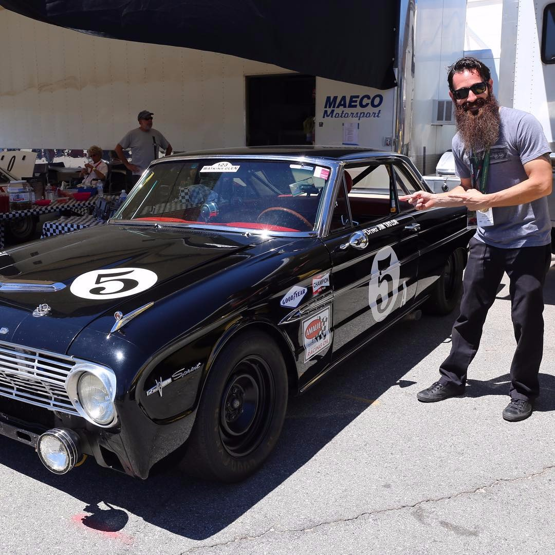 Aaron Kaufman pointing towards a VinRacer Ford Falcon