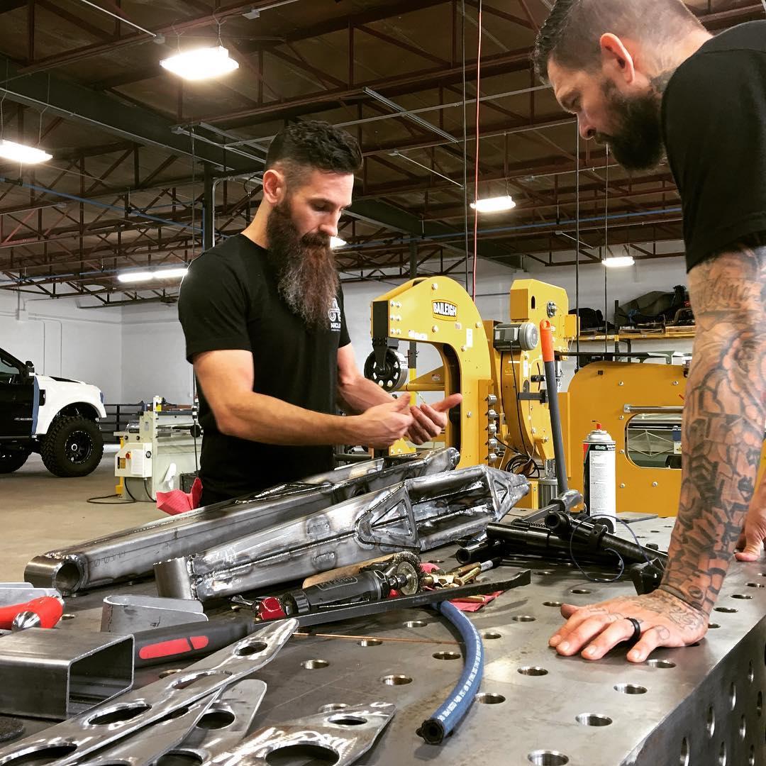 Aaron Kaufman working in the tools alongside a friend