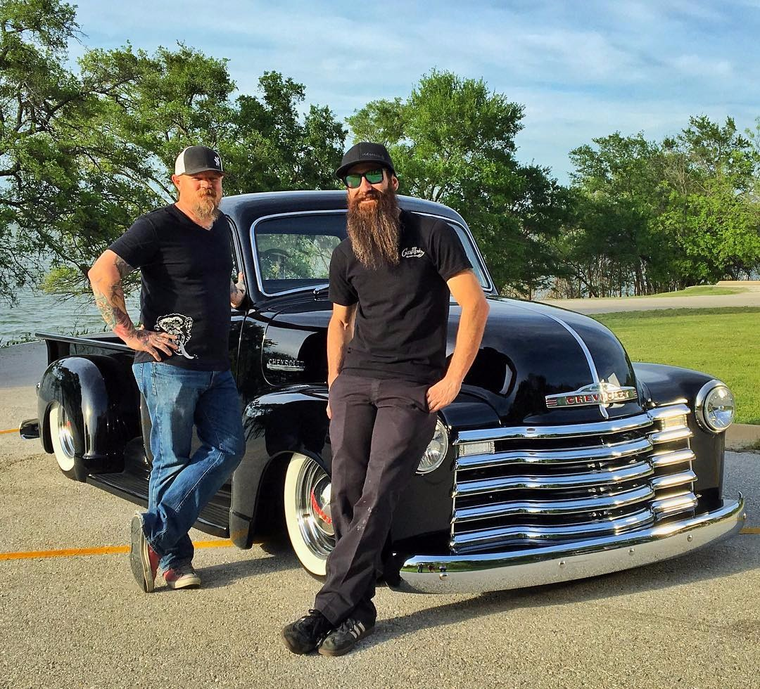 Former Gas Monkey Garage mechanic Aaron Kaufman with Gas Monkey Garage painter Mike Coy posing in front of a shiny black car.
