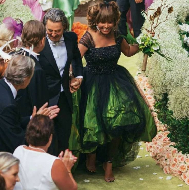Erwin Bach is holding Tina Turner's hand. He is wearing a black suit with white shirt. Tina is wearing a green gown.