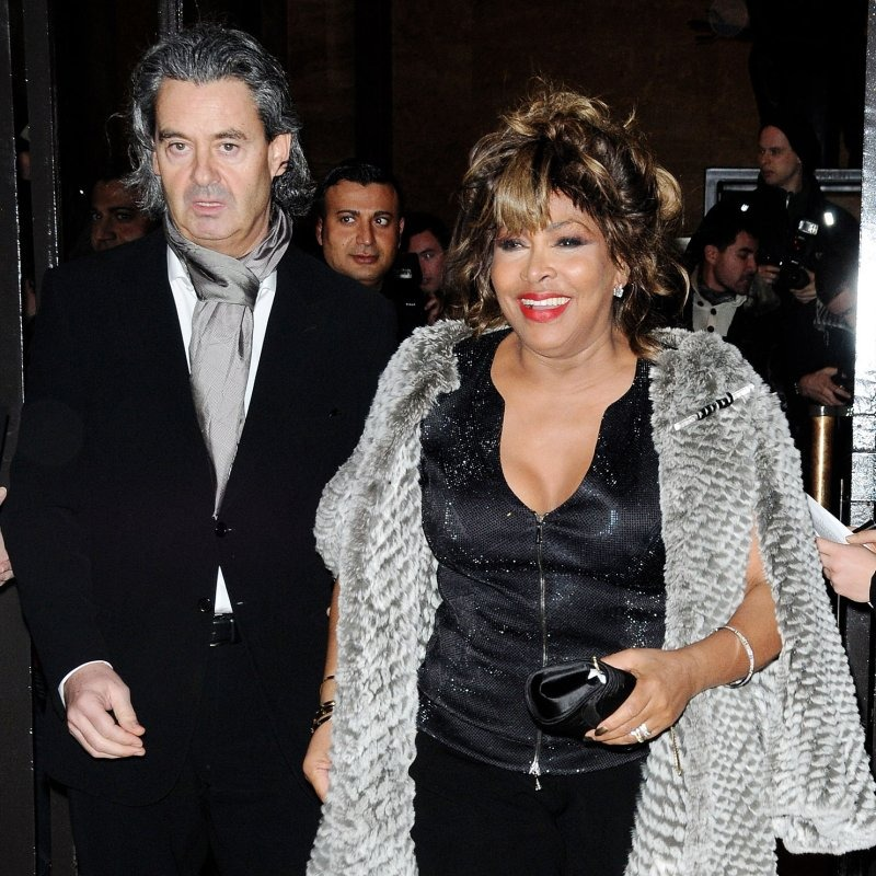 Erwin bach is with his wife Tina Turner. Tina is smiling and wearing a black dress. Erwin is wearing black suit and silver scarf.