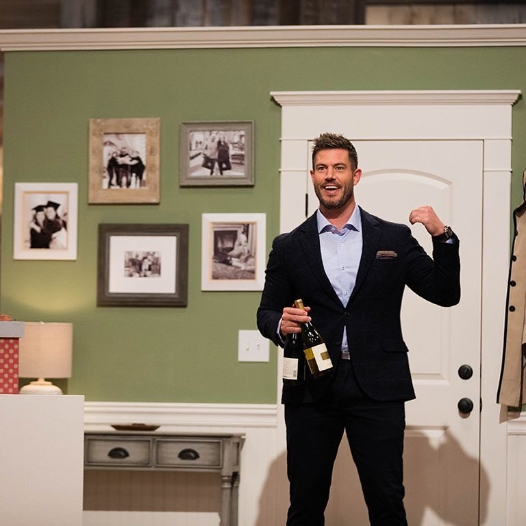 Jesse Palmer on the sets of Holiday Baking Championship. Jesse is in his black suit holding two champagne in one hand and pointing at the door with a happy face from the other hand.
