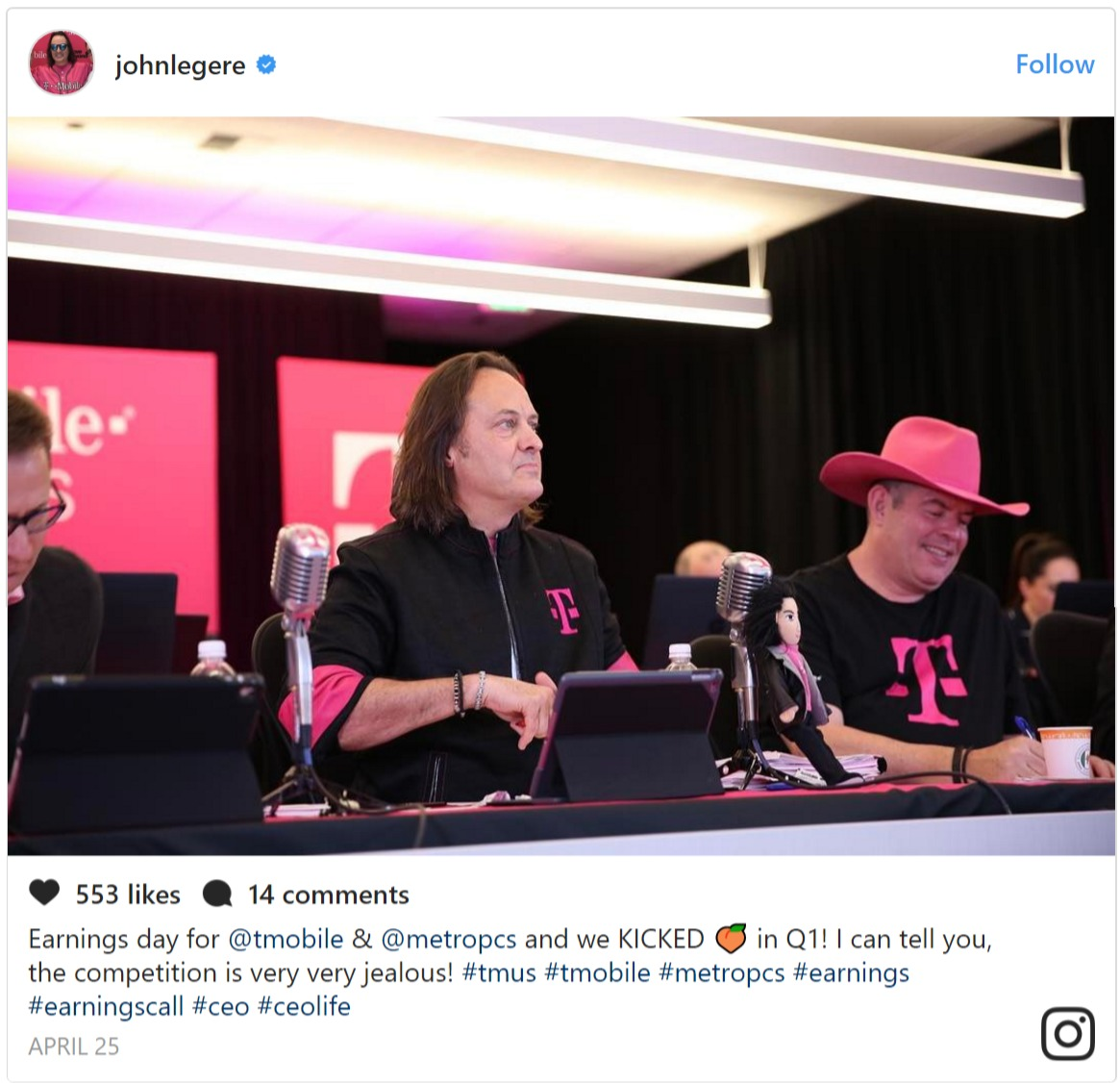 John Legere sitting behind a desk between two other men, one of them is wearing a magenta cowboy hat