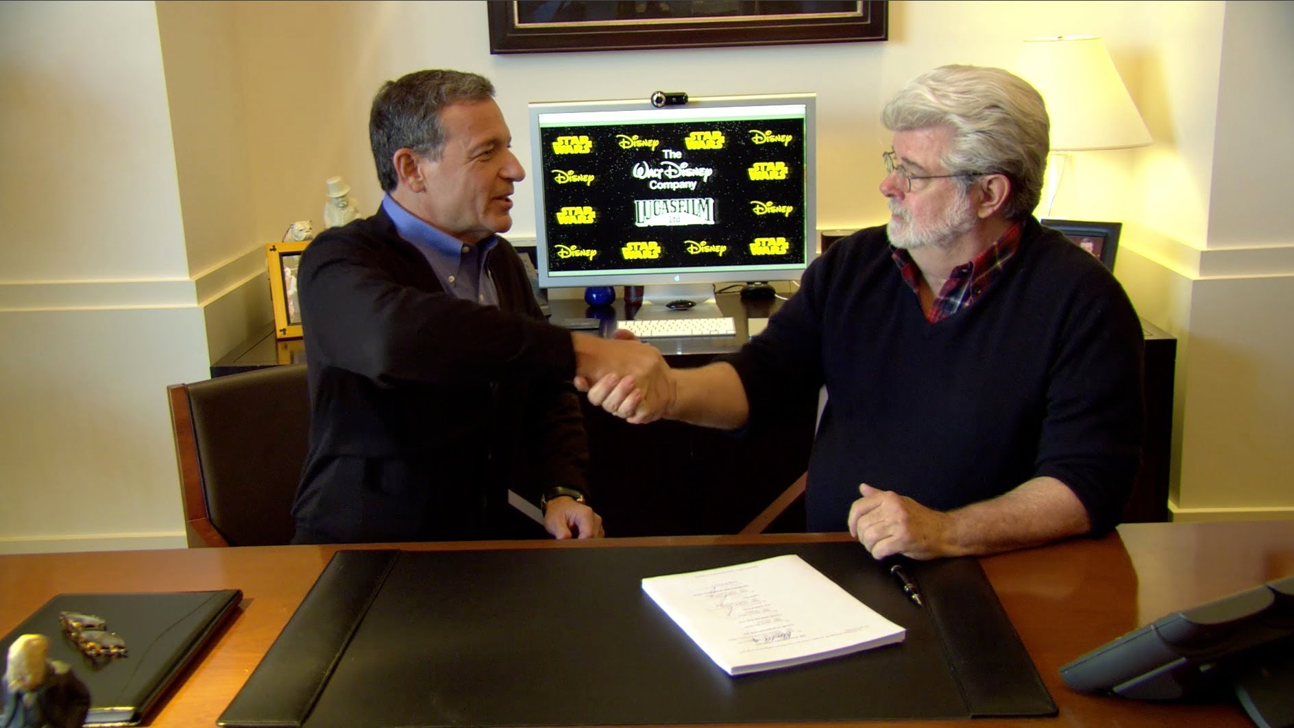 Walt Disney CEO, Bob Iger and producer George Lucas shakes hand during sign and discussion about Disney Lucasfilm purchase.