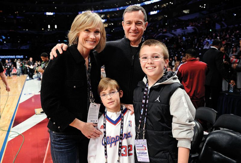 Bob Iger and his wife Willow Bay posing for a camera during basketball game with their two sons.