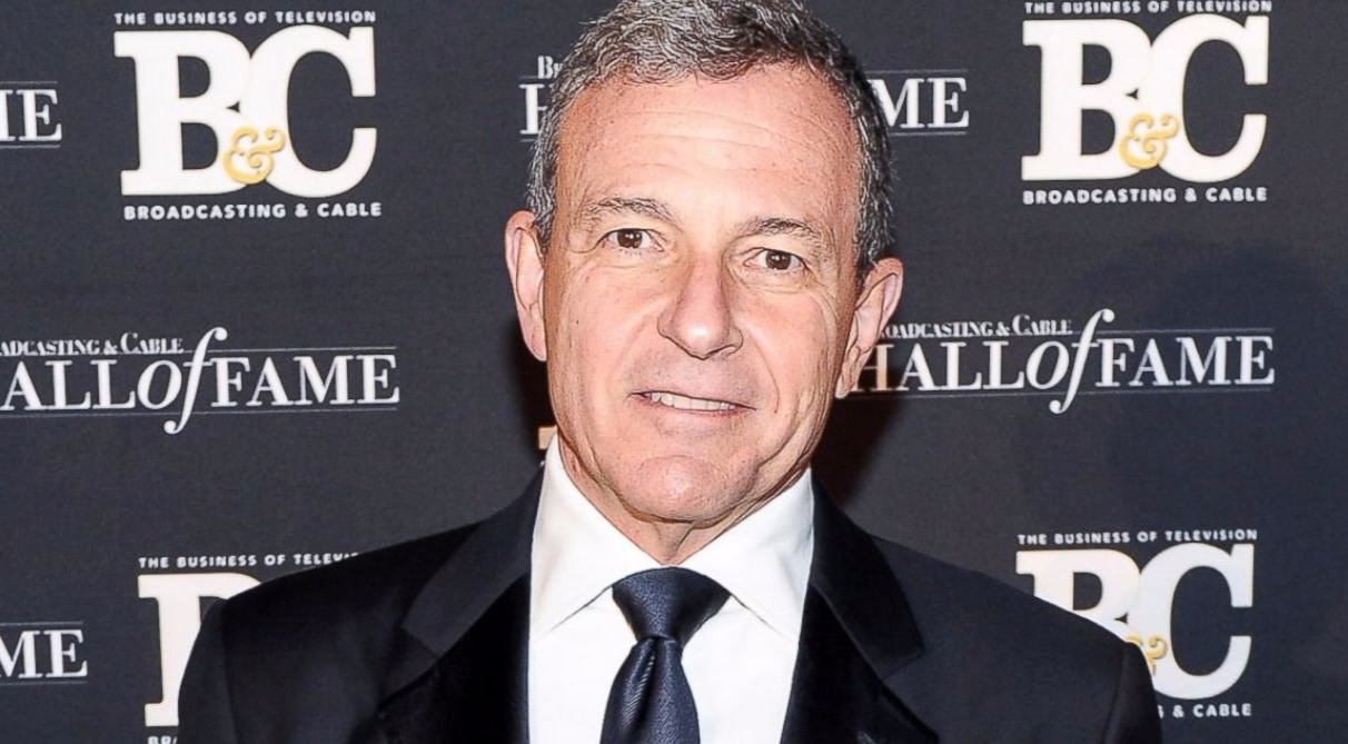 CEO Bob Iger suited in black coat and black tie. He is smiling at the camera for photo shoot.