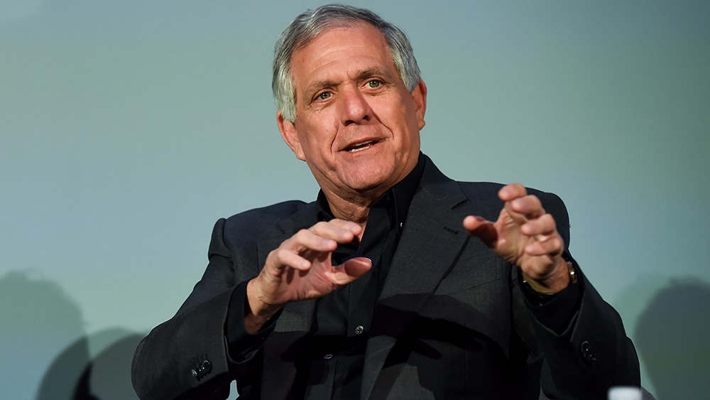 Leslie Moonves is using his hand's gesture on explaining his views in a business event. He is dressed all formal with black shirt and coat.