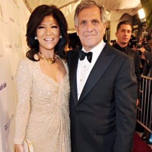 Leslie Moonves and his current wife Julie Chen attending an event together. Julie looks beautiful in her low neck glittery dress. The couple is standing close and smiling for the camera.