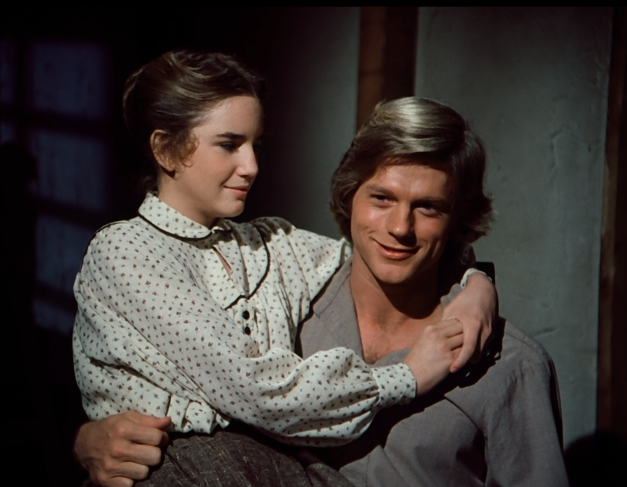 Laura Ingalls on the lap of Almanzo in the show Little House on the Prairie