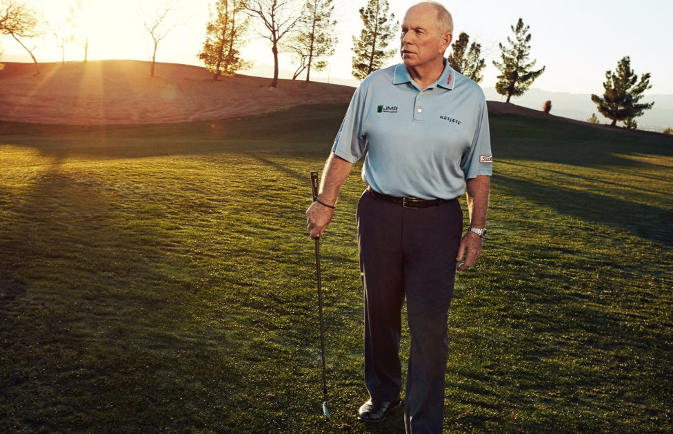 Butch Harmon looking to the right standing in the middle of golf course with a golf club in his hand