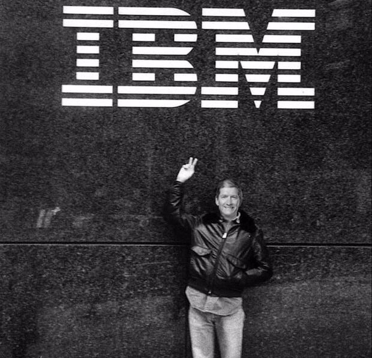 Tim Cook striking victory sign beneath the IBM logo