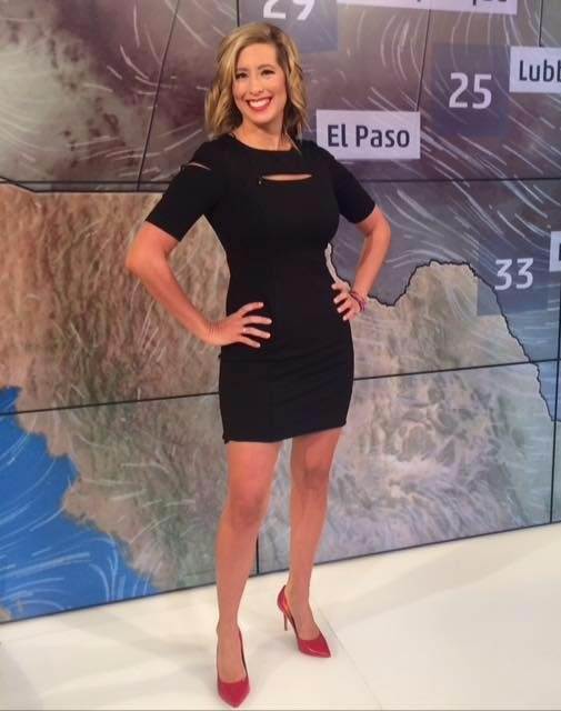 Stephanie Abrams is standing in a black short dress exposing her long legs and a red heel.