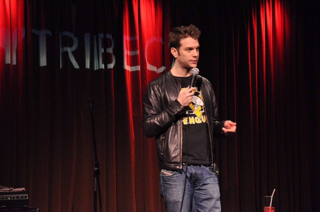 Anthony Jeselnik is wearing a casual outfit with t-shirt and jeans and black leather jacket. He holds the mic while delivering his speech to the audience.