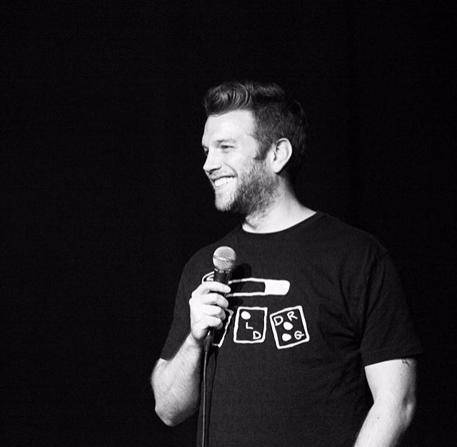 Anthony Jeselnik is facing sideways, he is looking too cute with the smile that he has put on. He is holding a mic, delivering his sarcastic comedy.