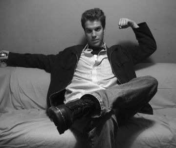 Anthony Jeselnik sitting comfortably on a sofa and showing off his hand punch to the camera.