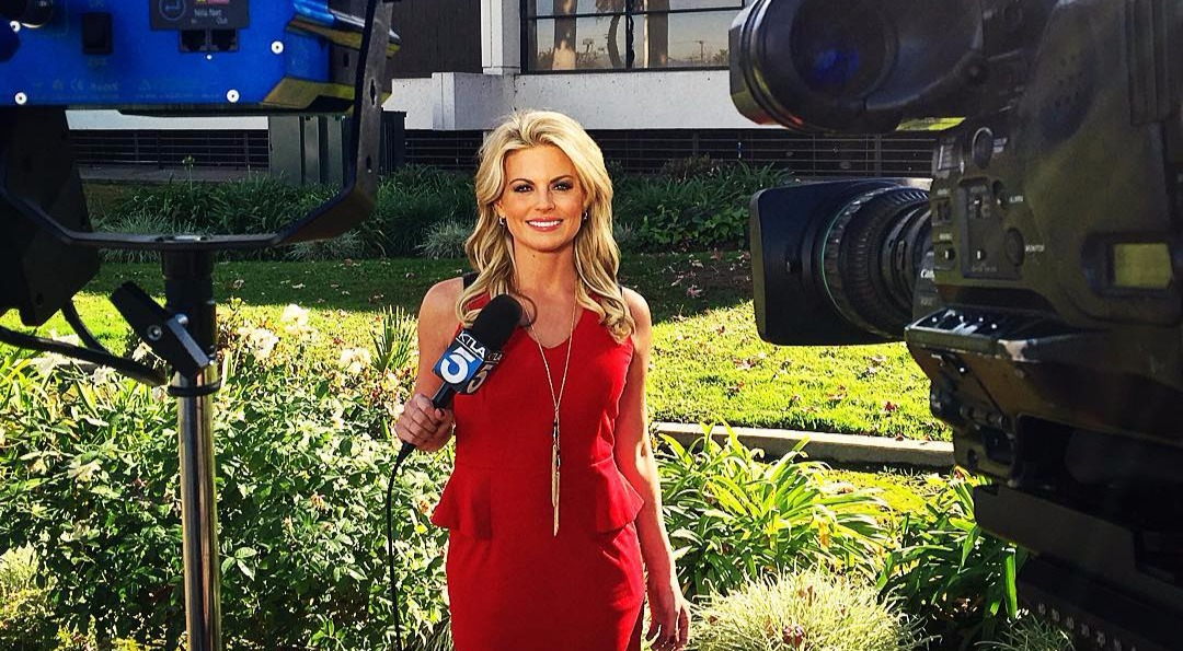 Courtney Friel in a red dress in front of cameras